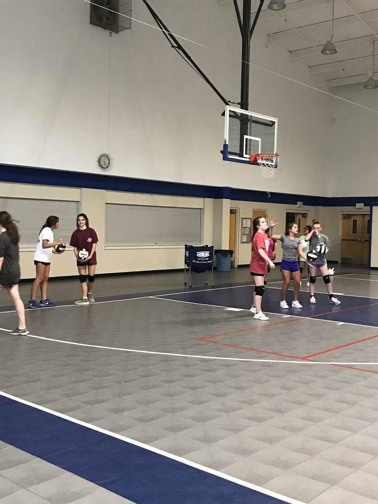 IHM 7th and 8th grade team members get some serving tips from CTK players.